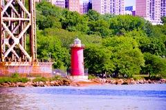 在一座桥梁旁边的红色灯塔在河前面有绿色背景 免版税库存图片