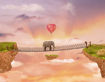 在一座桥梁的大象在与气球的天空 免版税库存图片