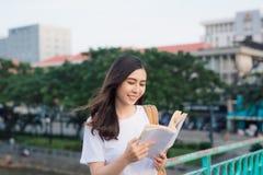 在一座桥梁的年轻美丽的女孩阅读书有城市视图 免版税库存图片