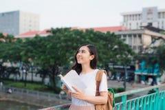 在一座桥梁的年轻美丽的女孩阅读书有城市视图 库存图片