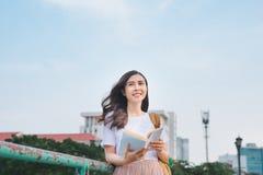 在一座桥梁的年轻美丽的女孩阅读书有城市视图 免版税库存照片