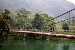 在一座桥梁的摩托车在绿色密林包围的河 库存照片