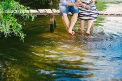 在一座桥梁的时兴的凉快的夫妇在水附近,关系,浪漫史,腿,生活方式-概念 免版税库存照片