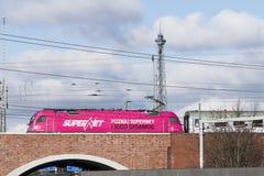 在一座桥梁的桃红色机车在Funkturm无线电铁塔柏林前面的一条高速公路 免版税库存图片