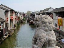 在一座桥梁的石狮子在一个水道在苏州 免版税库存照片