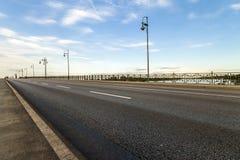 在一座桥梁的空的柏油路在河 图库摄影