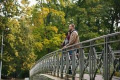 在一座桥梁的年轻夫妇在秋天 免版税图库摄影