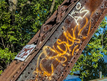 在一座生锈的钢火车桥梁的街道画 库存图片