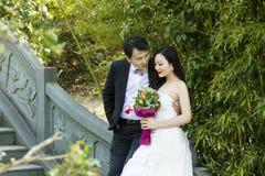 在一座石古老桥梁站立在shui bo公园在上海的中国夫妇` s婚礼照片 免版税图库摄影