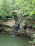 在一座石桥梁下的瀑布 库存照片