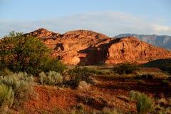 在一座红色岩石山的日出与沙漠风景 免版税库存照片