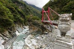 在一座红色茨木桥梁前面的大理石狮子雕象在Taroko 免版税库存照片