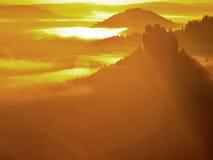 在一座美丽的山的庄严金黄日出 砂岩岩石从金有雾的谷背景增加了 免版税库存图片