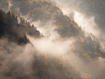 在一座美丽的山的秋天日出在反向内 小山小条大雾峰顶  图库摄影