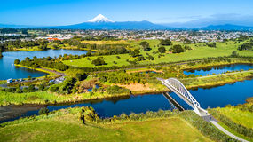 在一座美丽的桥梁的鸟瞰图横跨与塔拉纳基山的一条小小河背景的 新西兰 库存图片