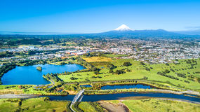 在一座美丽的桥梁的鸟瞰图横跨与塔拉纳基山的一条小小河背景的 新西兰 免版税图库摄影