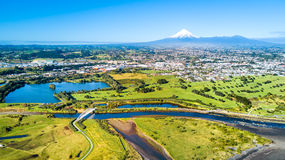 在一座美丽的桥梁的鸟瞰图横跨与塔拉纳基山的一条小小河背景的 新西兰 免版税库存照片