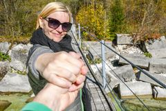 在一座老木吊桥的愉快的微笑的妇女身分,当握胳膊时 免版税库存图片