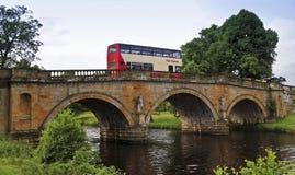 在一座老桥梁的一辆公共汽车在英国 免版税图库摄影