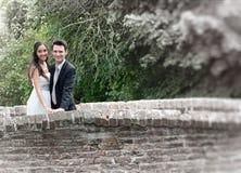 在一座老石桥梁的浪漫愉快的夫妇 免版税库存照片