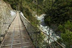 在一座豪华的山的步行吊桥在岩石河上 免版税库存照片