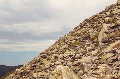 在一座陡峭的山的倾斜的石头储蓄 免版税库存照片