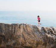 在一座高山的运动妇女奔跑 免版税库存照片
