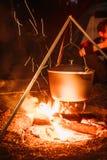 在一开火的煮沸的罐在被弄脏的背景 图库摄影