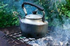 在一开火的老葡萄酒金属水壶在自然 库存照片
