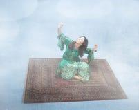 在一张不可思议的地毯的阿拉伯女孩飞行 免版税库存照片