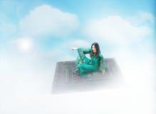 在一张不可思议的地毯的阿拉伯女孩飞行 免版税图库摄影
