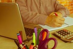 在一张书桌的商人在办公室键入在便携式计算机和计算器上的 免版税库存图片