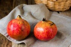 在一张亚麻制洗碗布的五颜六色的红色石榴与柳条筐在背景中,在木桌上 免版税图库摄影