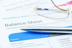 在一张公司资产负债表的蓝色圆珠笔与眼睛玻璃 免版税库存照片