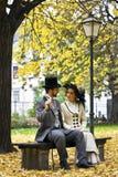 在一张公园长椅的古板的穿戴的夫妇在秋天。 库存图片