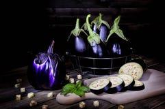 在一张古色古香的木桌上的新鲜的紫色茄子 免版税库存图片