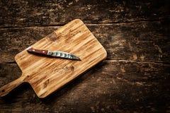 在一张困厄的木桌上的空的砧板 免版税库存图片