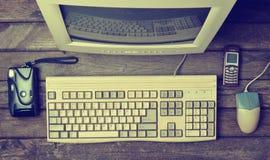 在一张土气木书桌上的减速火箭的固定式计算机,葡萄酒工作区 显示器,键盘,计算机老鼠,顶视图,平的位置 图库摄影