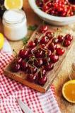 在一张土气木桌上的新鲜的红色樱桃 成熟樱桃我o 免版税图库摄影