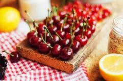 在一张土气木桌上的新鲜的红色樱桃 成熟樱桃我o 库存照片