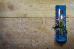 在一张土气木桌上的简单的圣诞节假日餐位餐具与中世纪利器 免版税图库摄影