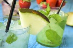 在一张土气蓝色桌上的刷新的瓜mojito 免版税库存图片