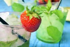 在一张土气蓝色桌上的刷新的草莓mojito 免版税图库摄影