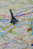 在一张地图的巴黎名字与红色埃佛尔铁塔缩样 免版税库存图片