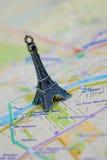 在一张地图的巴黎名字与红色埃佛尔铁塔缩样 免版税图库摄影