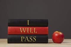 在一张学校书桌上的三本书用一个红色苹果 免版税库存照片
