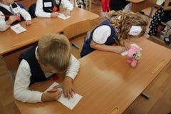 在一张学校书桌的学生在一个教训在学校-俄罗斯莫斯科第一所高中头等b - 2016年9月1日 免版税库存照片