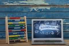在一张学校桌上的计算机与在屏幕上的学校象 免版税图库摄影