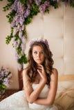 在一张床上的新娘与丁香 免版税库存照片