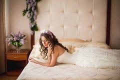 在一张床上的新娘与丁香 免版税库存图片
